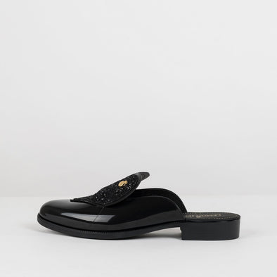 Black synthetic slide mules with a large heart applique in squins