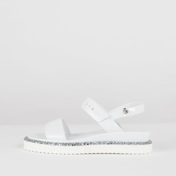 White synthetic sandals secured with na ankle buckle and with a grey glittery sripe lining the sole