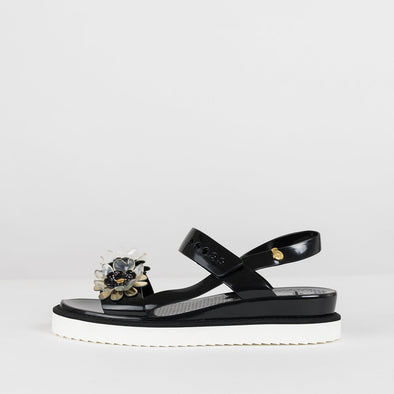 Sandals with two-straps and ankle buckle in black glossy synthetic with white rubber sole and acrlic flower appliques