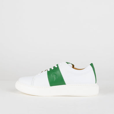 White leather sneakers with green strap and tongue.