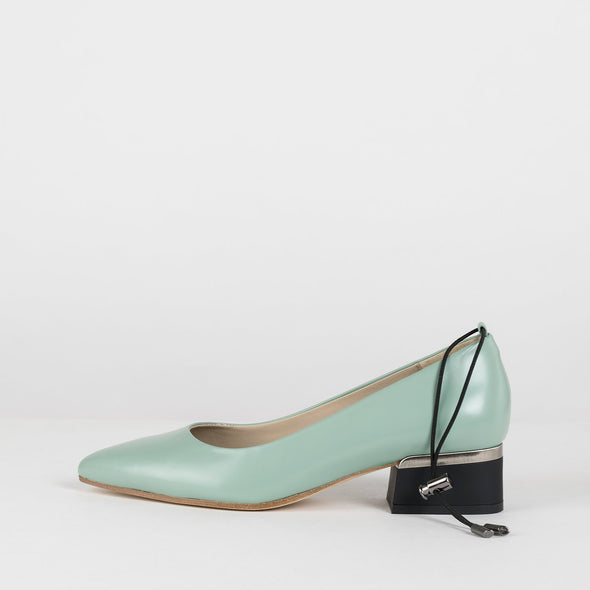 Mint-green pumps in leather with thin adjustable ankle elastic and short block heel in black with silver metallic applique