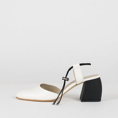 Ivory white pointed toe pump sandals in leather with thin black elastic ankle ties and block comma heel in black