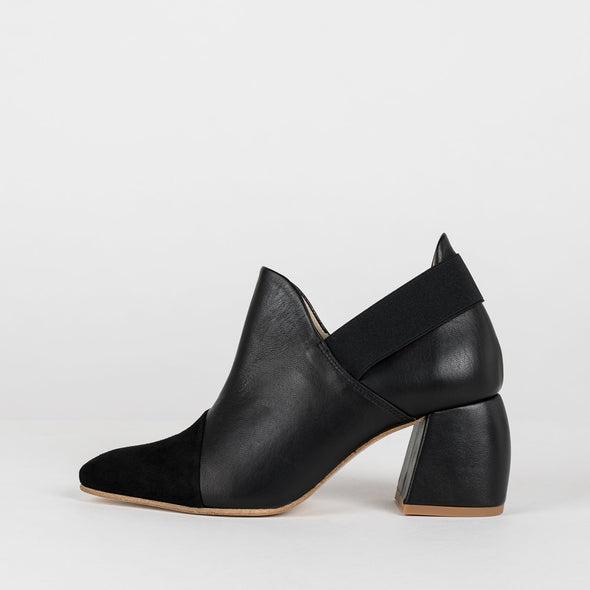 Pointed toe ankle boots in black leather with matching suede toe panel and decorative black elastic lining the ankle