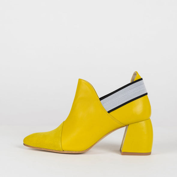 Pointed toe ankle boots in canary yellow leather with matching suede toe panel and decorative black elastic lining the ankle