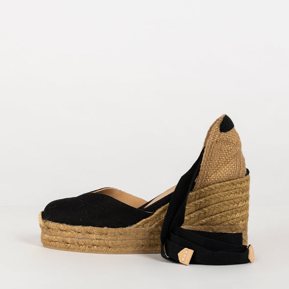 10cm-wedge espadrille and 2cm platform, made of canvas and natural jute. Jute-string and cotton heel. Tied to the ankle with laces.