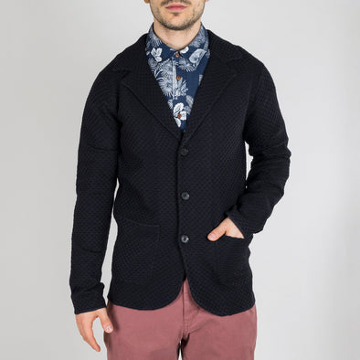 Dark colored cardigan featuring a structured wool blend knit and notch lapels.