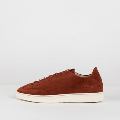 Minimalist low sole laced sneakers in rust orange suede with subtle perforation lining details