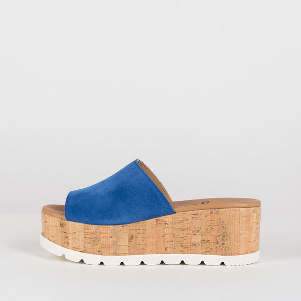 Platform slide sandals in cobalt blue suede with flatform cork sole and white rubber sole reinforcement