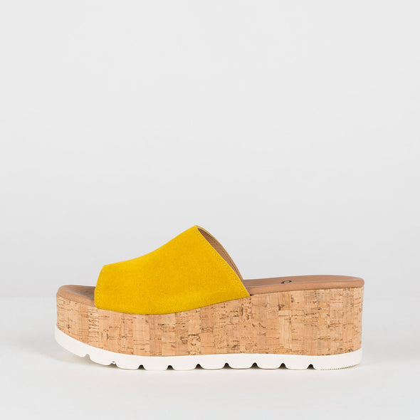 Platform slide sandals in canary yellow suede with flatform cork sole and white rubber sole reinforcement
