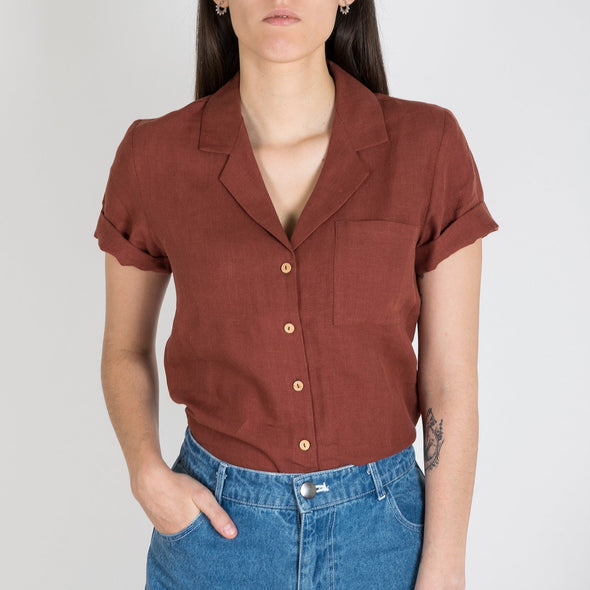 Terracotta colored shirt with short sleeves and one pocket.