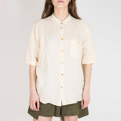 Oatmeal colored shirt with cross buttoning and two front pockets.