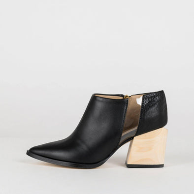 Geometric pointed toe ankle boots in black leather with a vinyl detail.