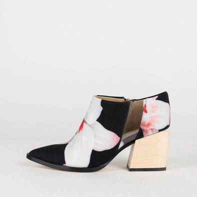 Geometric pointed toe ankle boots with a floral pattern and vinyl detail.