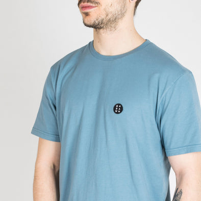 "Stone blue t-shirt with ""Essential"" patch on the chest."