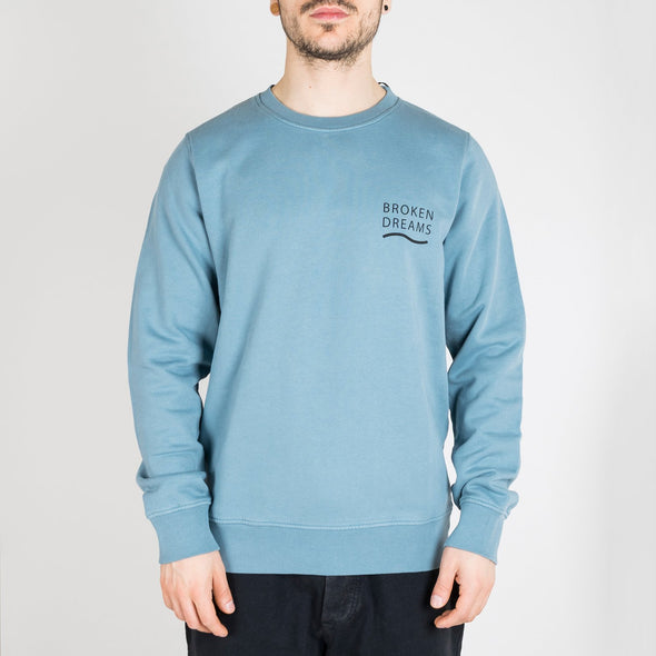 "100% organic cotton classic crew neck in light blue with ""Broken Dreams"" print."