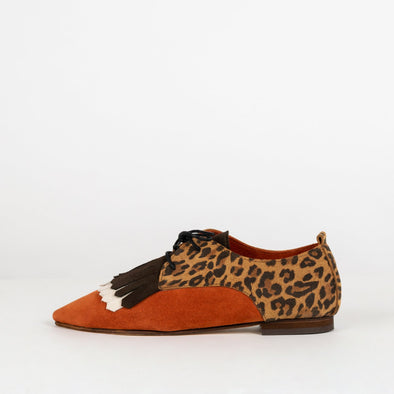 Bright orange ankle shoes with borwn and white fringe and leopard pattern.