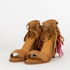 Camel suede heeled sandals with red, orange and pink fringe at the back.