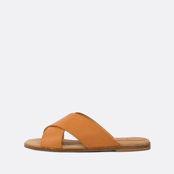 Minimalist cross-strap slides in camel brown leather.