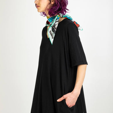 Black oversized V-neck dress featuring side pockets and a curved seam.