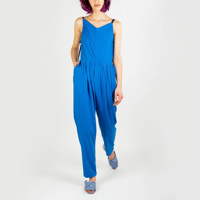 Organically designed blue catsuit featuring a high V-neck, crossed back straps and overlapped detailing at the front.