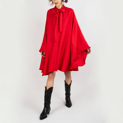 Loose satiny red dress with wrist cuffs and collar strap.