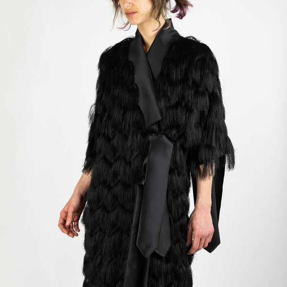 Black short kimono dress with fringes, a distinct collar and straps to tie at the front and at the sleeves.