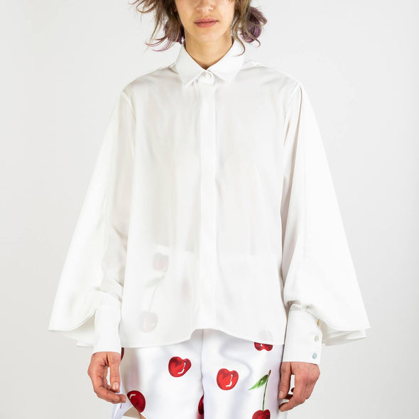 Long sleeved white shirt with cape over the shoulders.