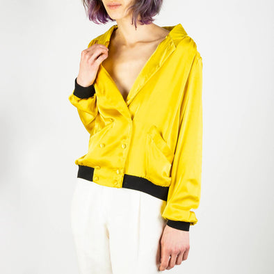 Yellow satiny blazer style jacket with black details.