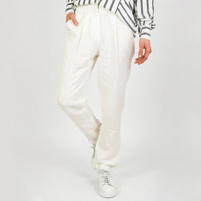 Minimalist pleated trousers in white linen.