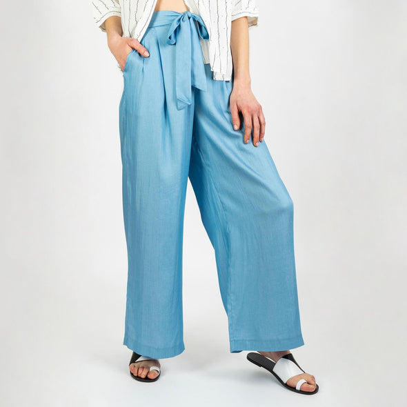 Loose high waisted trousers in a light indigo color with a belt to tie at the waist.
