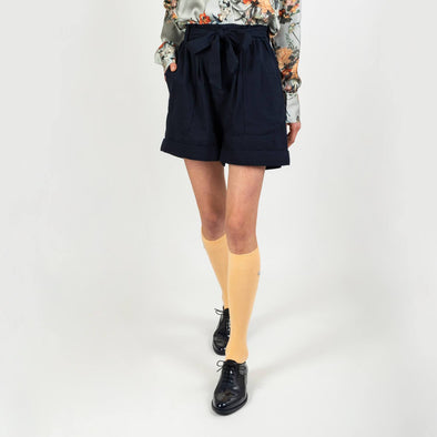 Navy blue cotton shorts with big front pockets and a strap to tie at the waist.