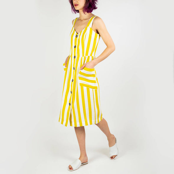 Mid-length white dress with wide yellow stripes, V-neck and front pockets.