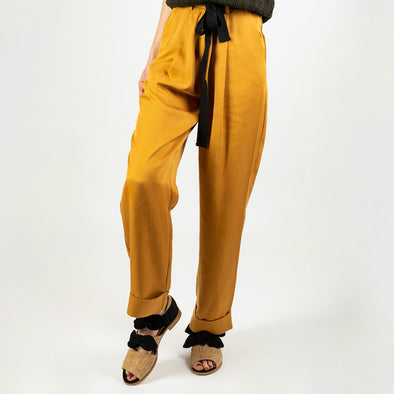 Slightly satiny camel fluid trousers featuring a black belt and a zipper at the waist.