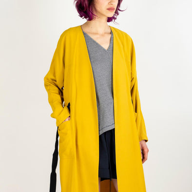 Yellow trench coat with a black belt and a pocket at the waist.