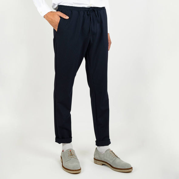 Navy blue slightly fitted trousers featuring a strap for extra comfort.