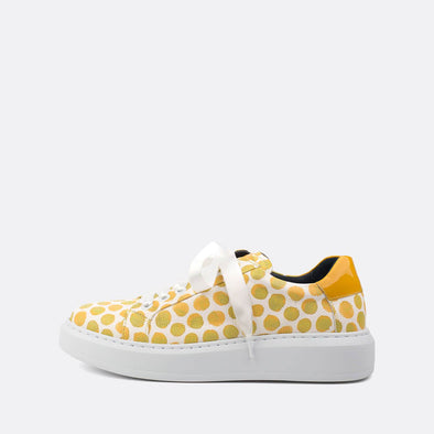 Textured leather white sneakers with yellow colored dots and satin laces.