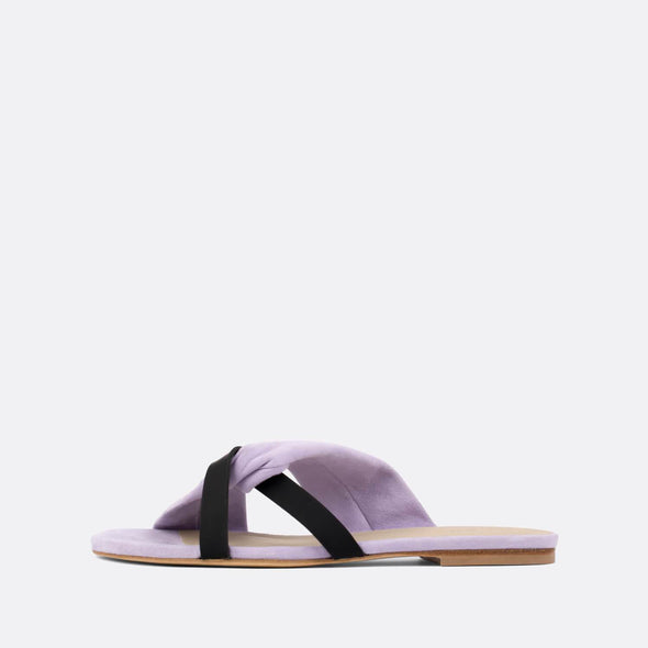 Elegant pastel purple suede cross-strap slides with black leather detail.