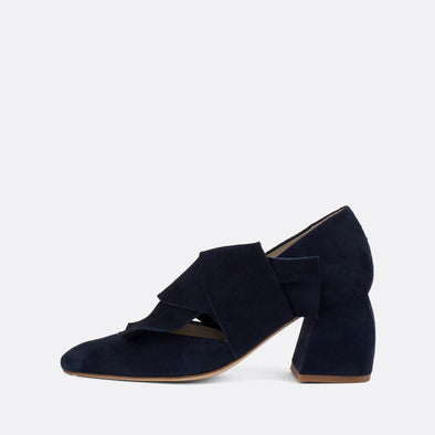 Striking suede pumps in a deep blue shade, featuring an overlapping strap with large bow effect.