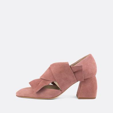 Striking suede pumps in a light pink shade, featuring an overlapping strap with large bow effect.