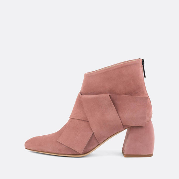 Striking suede ankle boots in a light pink shade, featuring an overlapping strap with large bow effect.