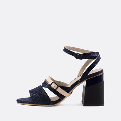 Elegant navy blue heeled open sandals with irreverent pattern and black block heel.