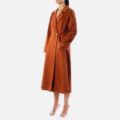 Copper matte double-breasted coat with side pockets and white buttons to the front.