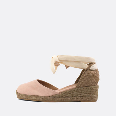Light pink wedge espadrilles made of canvas and natural jute with beige straps.