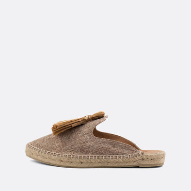 Desert-sand babouche mules with pompon detail on the instep and natural jute sole.