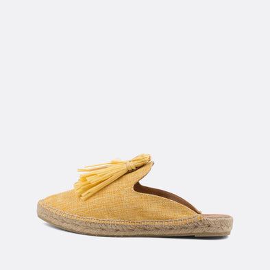 Yellow babouche mules with pompon detail on the instep and natural jute sole.