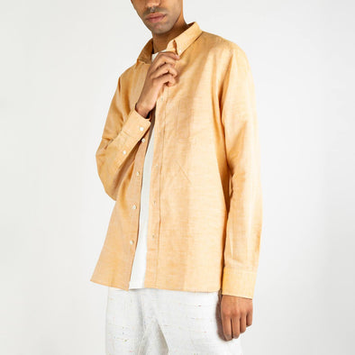 Long sleeved shirt in a orangy golden shade featuring a front chest pocket.