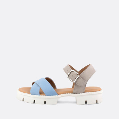 Flat cross-strap sandals in placid blue and grey featuring a distinct white track sole.