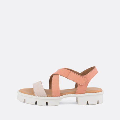 Flat cross-strap sandals in morganite peach featuring a distinct white track sole.