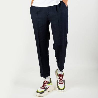 Navy blue slightly fitted 7/8 pants in a light seersucker with an elasticated belt on the back and thin pleats on the front.