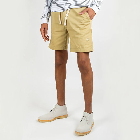 Beige cotton shorts with elastic waist and embossed label in the back pocket.